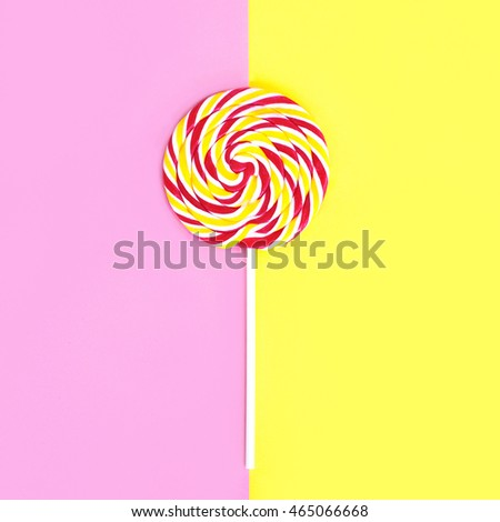 Colorful lollipop caramel on stick over pink yellow background top view
