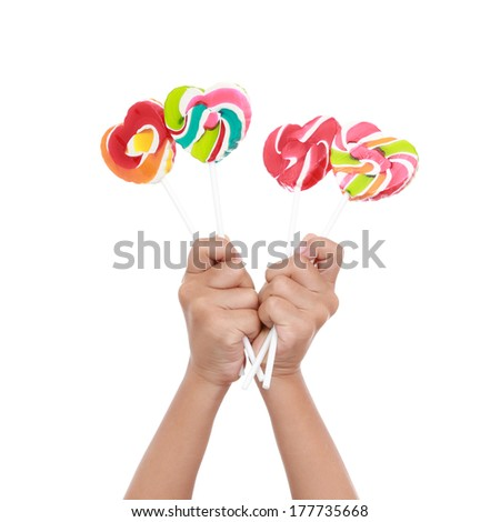 Colorful lollipop on children hand  isolated on the white  - stock photo