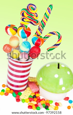 Colorful lollipops in a jar and more candies and a piggy bank in a table. Kids birthday table setting