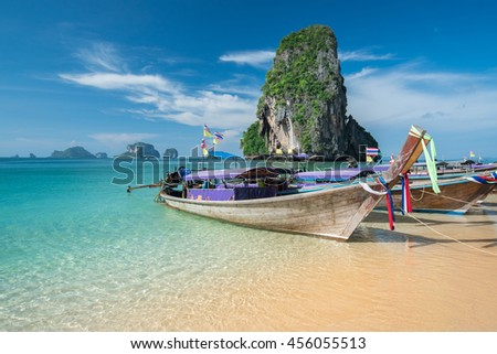 Colorful long tail boats at beautiful Ao Nang beach on a background of blue sky and azure sea and limestone rocks, Phi Phi Islands, Thailand