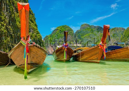 Colorful long tail boats at Maya Bay heavenly beach on a background of blue sky and azure sea and amazing limestone rocks, Phi Phi Islands, Thailand - stock photo