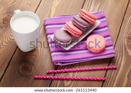 Colorful macaron cookies and cup of milk on wooden table background - stock photo