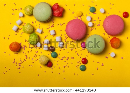 Colorful macaron pink and green color drop with many small jelly candies and dragee with marshmallow on yellow background