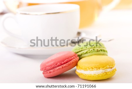 Colorful macaron with a cup of tea - Focus on the yellow one - stock photo