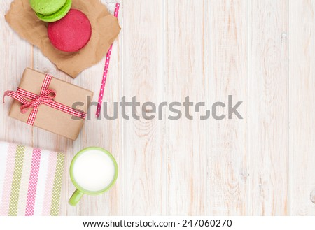 Colorful macarons, cup of milk and gift box on white wooden table with copy space - stock photo