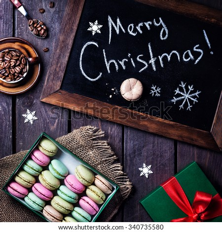 Colorful macarons near title Merry Christmas, cup of coffee and present Christmas boxes on wooden background - stock photo