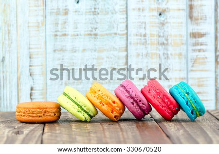Colorful macarons on vintage pastel background. Macaron or Macaroon sweet meringue-based confection. - stock photo