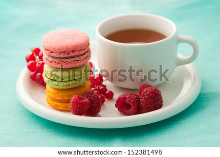 Colorful macarons with a cup of tea