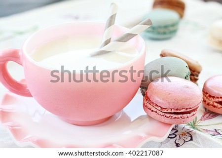 Colorful macarons with cup of milk. Extreme shallow depth of field with selective focus on pink macaron.