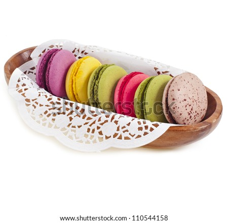 Colorful macaroones in a wooden bowl isolation on a white background