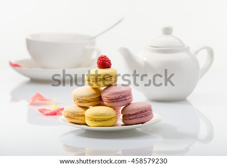 Colorful macaroons on a plate on background tea set - stock photo