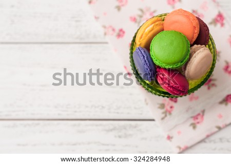 colorful macaroons on white wooden background - stock photo