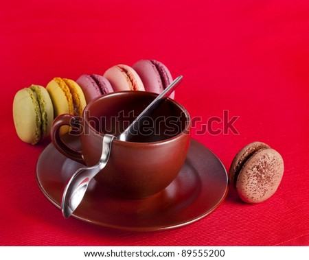Colorful  macaroons with coffee cup on a red  background
