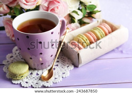 Colorful macaroons with cup of tea on wooden background - stock photo