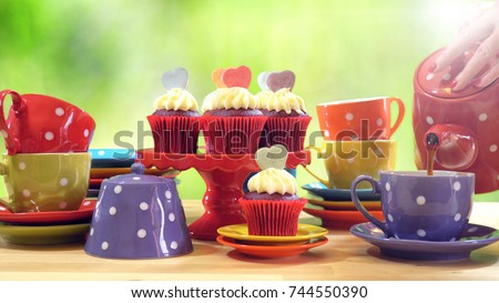 Colorful Mad Hatter style tea party with cupcakes and rainbow colored polka dot cups and saucers, with bokeh garden background and lens flare, pouring tea.