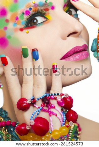 Colorful makeup and manicure with ornaments of different shapes and colors on the blonde girl.