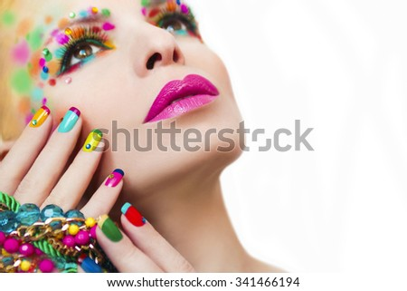 Colorful makeup and manicure with ornaments of different shapes and colors on the girl.
