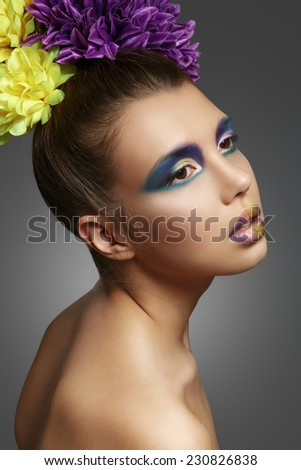 Colorful makeup. Beautiful model with a bouquet of flowers in the hairstyle.