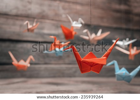 Colorful many origami paper cranes on wooden background - stock photo