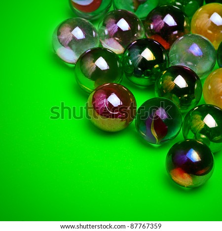 Colorful marbles over green background - stock photo