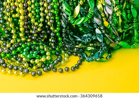 Colorful Mardi Gras beads on yellow background.