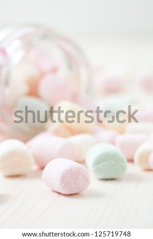 Colorful marshmallows in glass jar on light background