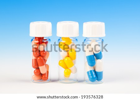 Colorful medical capsules in bottle, on blue background. - stock photo