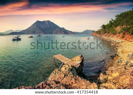 Colorful Mediterranean seascape in Turkey. Dramatic spring sunset in Adrasan bay with view of Moses Mountain. Artistic style post processed photo. - stock photo