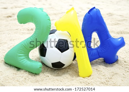 Colorful 2014 message with inflatable numbers and soccer ball football on sand beach - stock photo
