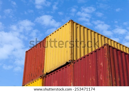 Colorful metal Industrial cargo containers are stacked under blue cloudy sky - stock photo