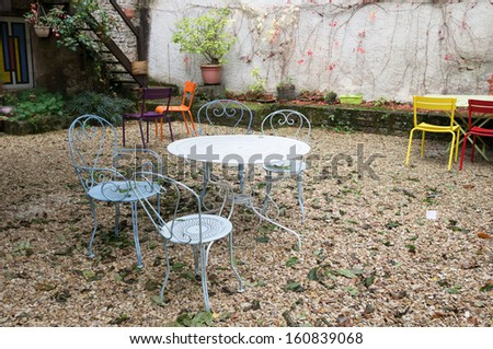 Colorful metal tables and chairs in a Patio and garden, noyers, france - stock photo