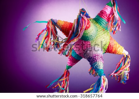 Colorful mexican pinata used in birthdays on a purple background - stock photo
