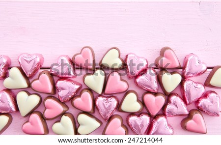 Colorful milk chocolates in heart-shapes on pink - stock photo