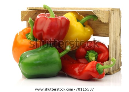 colorful mix of paprika's(capsicum) in a wooden box on a white background - stock photo