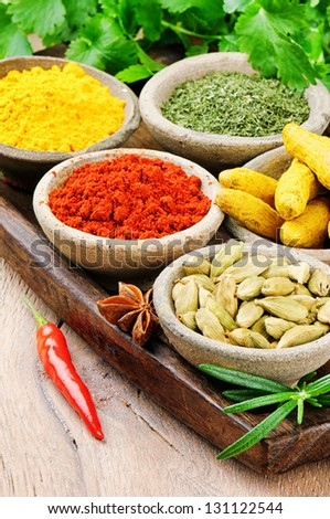 Colorful mix of spices on wooden table - stock photo