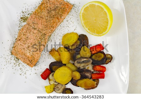 Colorful mixed purple, yellow and orange carrot pieces with crimini mushrooms along with poached wild sockeye salmon fillet topped with dill served with a lemon half.