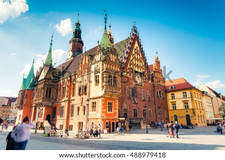 Colorful morning scene on Wroclaw Market Square with Town Hall. Sunny cityscape in historical capital of Silesia, Poland, Europe. Artistic style post processed photo.