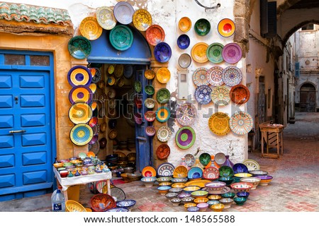 Colorful Moroccan faience pottery dishes on display in an alley outside a shop in the scenic fishing village of Essaouira, Morocco - stock photo