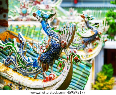 Colorful mosaic roof detail at the Linh Ung Pagoda in the Marble Mountains, Danang (Da Nang), Vietnam. The Marble Mountains is a popular tourist destination of Asia. Focus on the first sculpture.