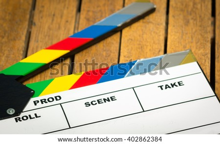 Colorful movie clapboard lying on wooden surface as seen from above - stock photo