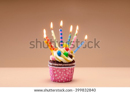 Colorful muffins with burning candles on them - stock photo