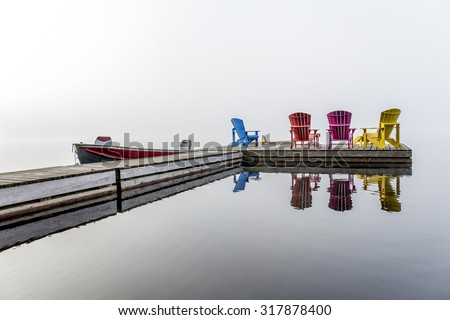 Colorful Muskoka Chairs Arranged on a Dock with a Small Motorboat on a Misty Morning - Haliburton, Ontario, Canada - stock photo