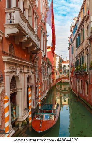 Colorful narrow lateral canal and pedestrian bridge in Venice with docked boats, Italy - stock photo