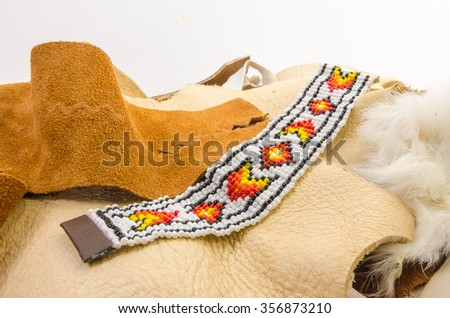 Colorful Native American Beaded Bracelet on scraps of leather and rawhide with white background and copy space. - stock photo