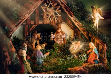 Colorful Nativity Scene with baby Jesus, Mary, Joseph, an angel and other famous religious figures of the bible, enhanced with rays of light for devotional mood - stock photo