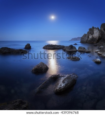 Colorful night landscape with full moon, lunar path and rocks in summer. Mountain landscape at the sea