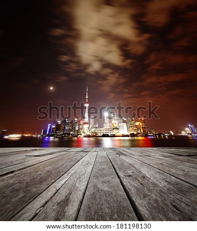 Colorful night lights of Shanghai city skyline in the horizon of an empty timber deck platform.   - stock photo