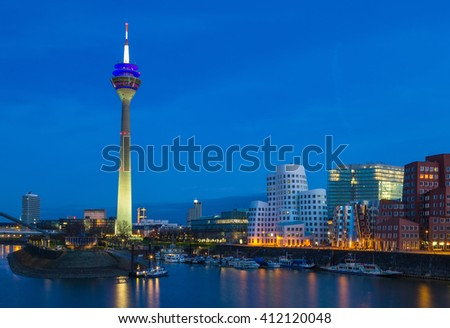 Colorful night scene of Rhein river at night in Dusseldorf. Rheinturm tower in the soft night light, Nordrhein-Westfalen, Germany, Europe.