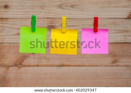 Colorful notes paper and a clothes pegs on wooden background