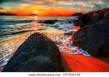 Colorful ocean bay sunrise with scenic rocks waves sand and bright clouds vacation destination - stock photo